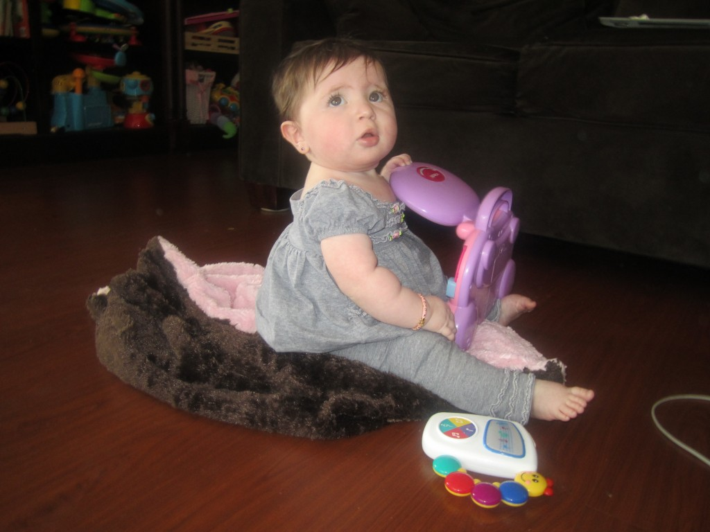 Baby Rochel sits with a large and heavy toy.