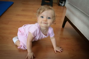a baby crawls on a wood floor