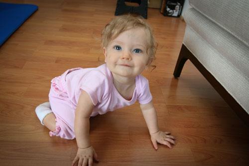 a baby crawls on a wood floor