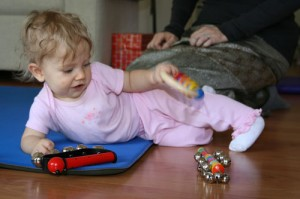 7-month-old baby balances on her side while playing with a rattle