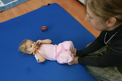 A seven month old baby feels her feet get pressed into the floor with her knees bent.