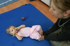 A baby focuses on the feeling of her feet pressing into the floor.