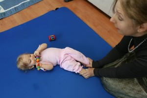 A baby scoots while in a Stellar Caterpillar motor skill lesson