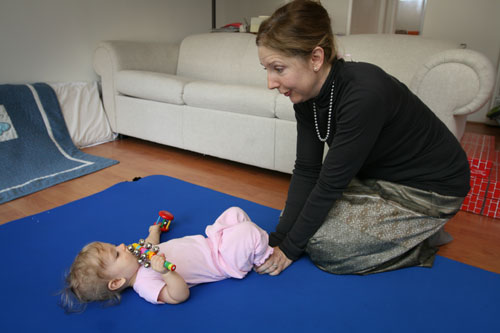 A baby prepares to scoot by pressing both feet into the floor.