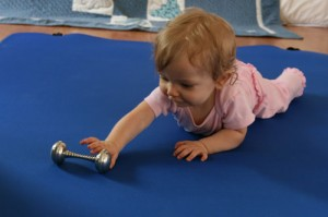 baby reaches to grasp a classic silver dumbell rattle