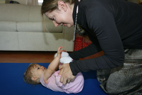 baby is on her back while teacher bends her knees to her chest