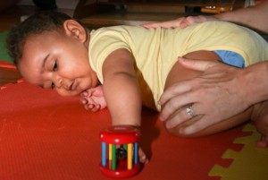 A baby receives motor skill instruction through hands-on guidance by her teacher.