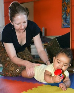 Donna Eshelman uses hands to show baby how to move her hips.