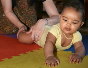 A Stellar Caterpillar instructor shows baby how to feel her leg initiate a roll.