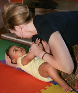 a baby is placed on the floor with her head supported by the teacher's hand
