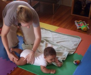 a baby plays on her tummy on the floor