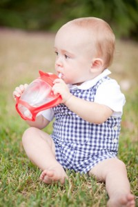 Baby drinks out of a Lollacup brand of sippy cup
