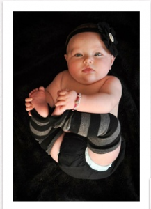 baby holds both feet with both hands and claps feet together