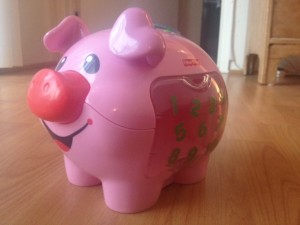 Transparent side door on the piggy bank allows baby to see where the coins arrive when deposited.