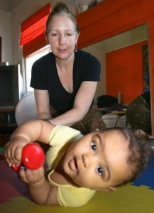 a baby holds a toy while rolling