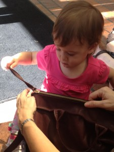 a toddler pulls the zipper on a purse