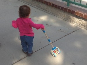 Baby drags push-toy behind her when walking.