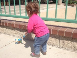 toddler pushes toy near edges of a wall